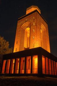 Bild des in gelb-orange beleuchteten Bismarckturms bei Nacht