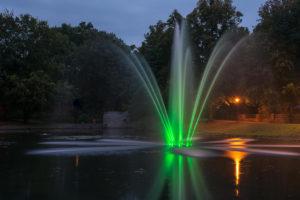 Springbrunnen mit grünen Lichtern bei Nacht im Hintergrund der Park