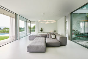 Designerleuchte Theo in einem lichtdurchflutetem Wohnzimmer mit großen Fenstern in Zürich