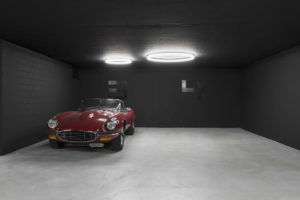 """Zwei Designer Ringleuchten """"TheO"""" in einer Tiefgarage in Zürich mit rotem Oldtimer"""