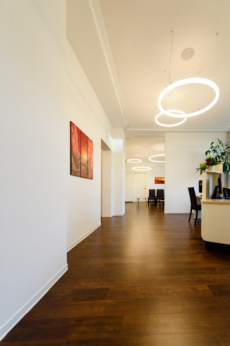 Flur Augenklinik Dr. Stoll mit Bildern an der Wand und Lampen an Decke