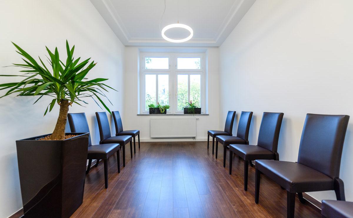 Wartezimmer Arzt mit Lederstühlen und kleiner LED-Ringleuchte an der Decke