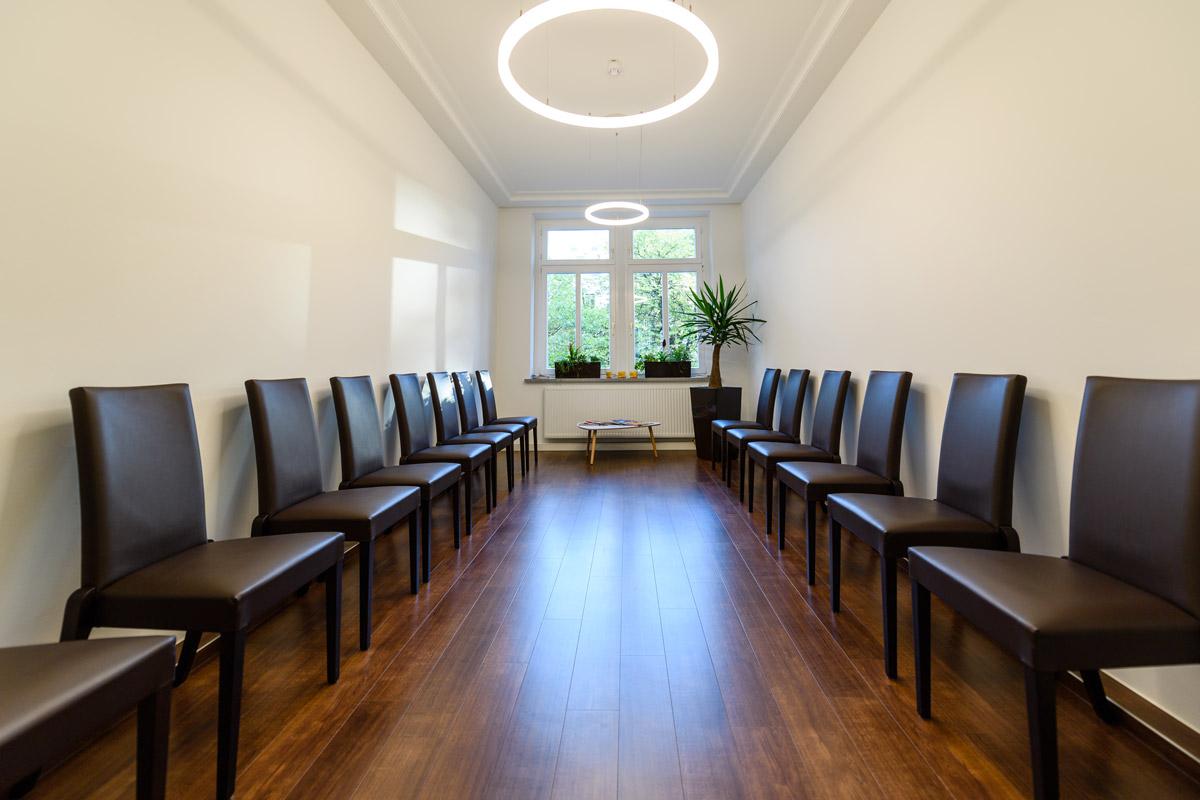 Wartebereich Praxis mit Stühlen und zwei LED-Deckenleuchten