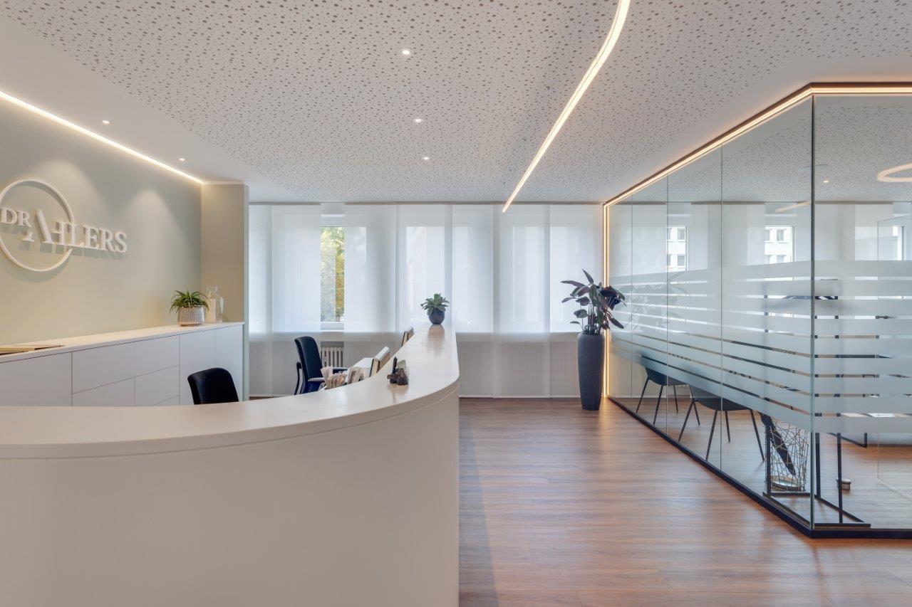 Empfangstheke Praxis Dr. Ahlers mit LED-Linien und indirekter Beleuchtung im Hintergrund