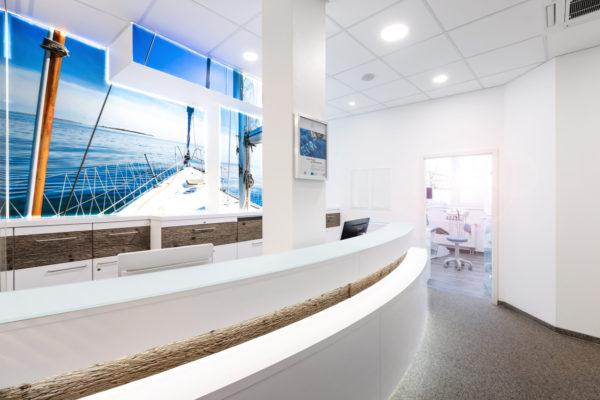 Empfangsthresen der Zahnarztpraxis mit hinterleuchteten Bild welches ein Boot und Meer darstellt.