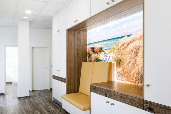 Flur Zahnarztpraxis mit Wartebereich mit LED Deckenleuchten und hinterleuchtetem Bild vor Sitzbank