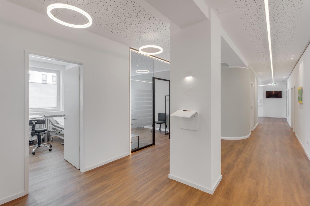 Flur derArztpraxis mit weißen Wänden LED-Ringleuchten und LED Linien an der Decke