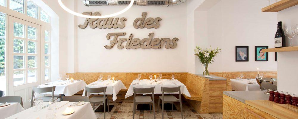 Restaurant-Ross Berlin mit Schriftzug Haus des Friedens und Designer Ringleuchte TheO
