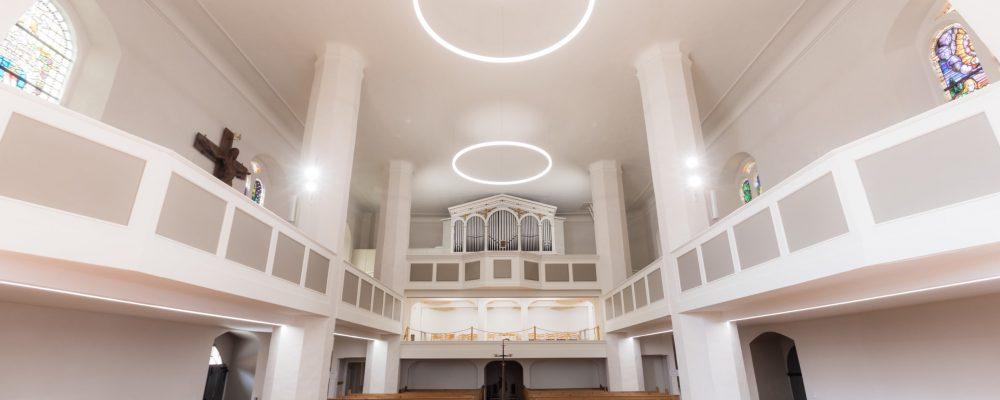 Blick über die Kirchenbänke in den Saal des Hauptschiffs - mit Ringleuchten an der Decke der Kirche